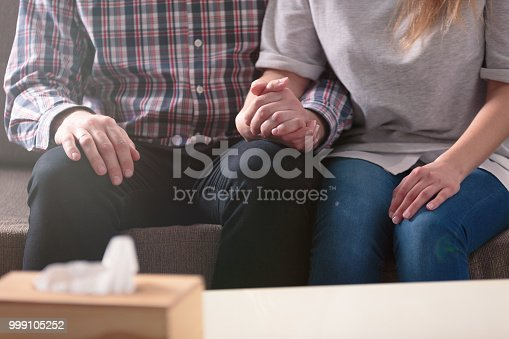 Close-up of a couple holding hands together while sitting on a couch during a therapy