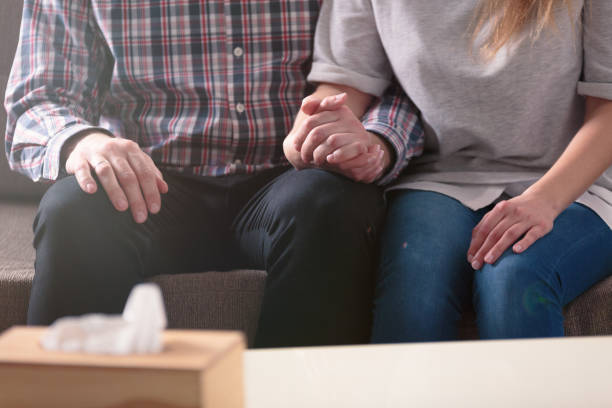 close-up of a couple holding hands together while sitting on a couch during a therapy - grief stock photos and pictures