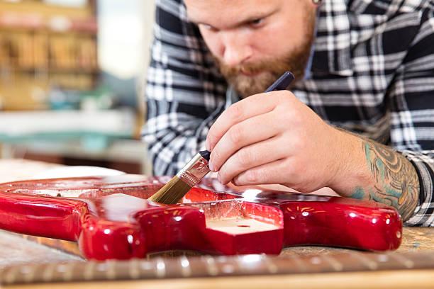 nahaufnahme eines handwerker malen gitarre in workshops - baroque tattoo stock-fotos und bilder