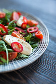 Closeup of a Creative  Caprese Salad on Wooden Table with added Red Peppers and Rucola