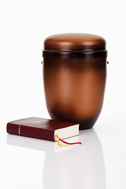 A close-up of a cremation urn next to a bible and rosary stock photo