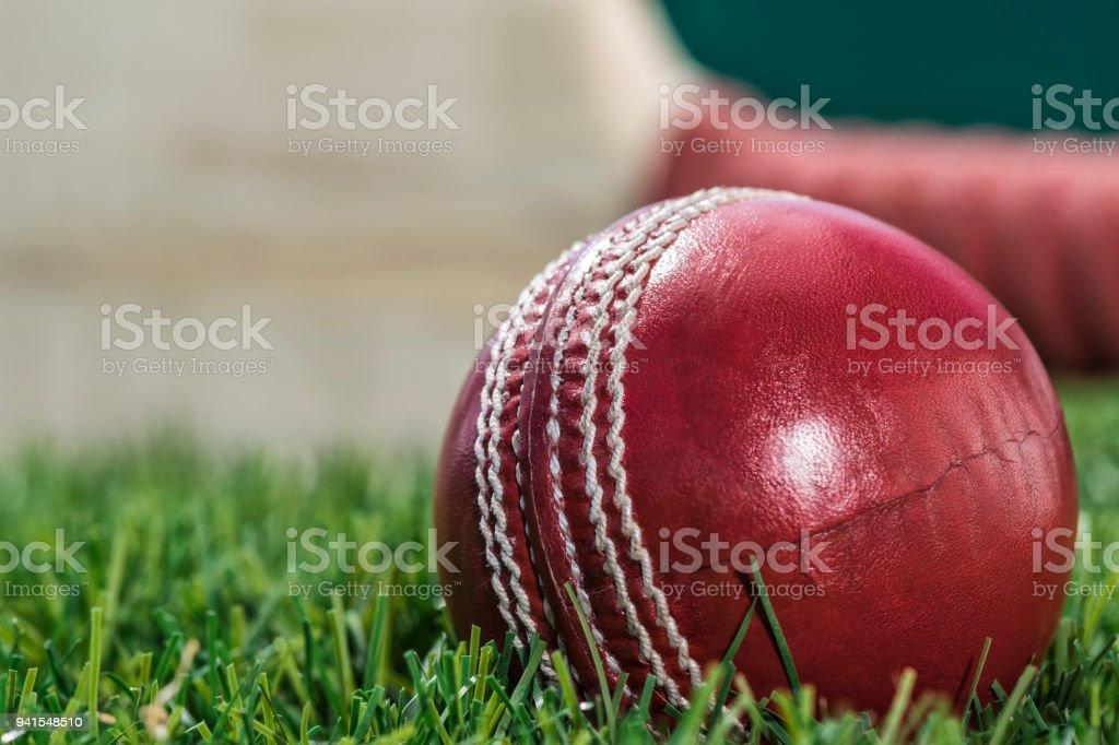 Eine Nahaufnahme von ein Cricketball sitzen auf der Wiese mit einem Schläger in Rasen – Foto