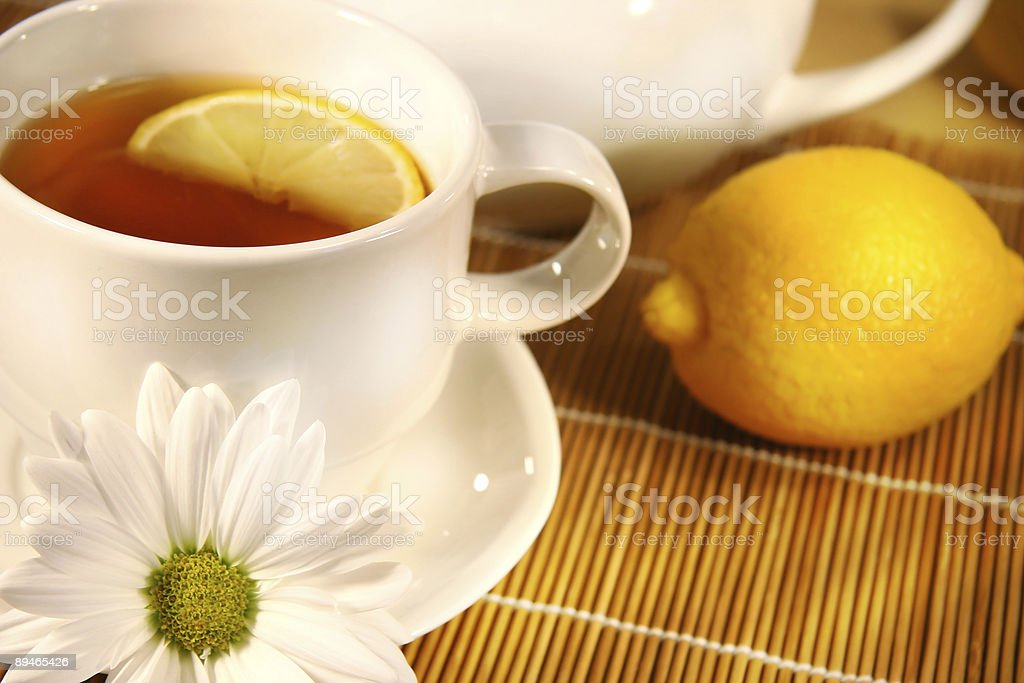 Close-up of a cup of tea with lemon slice on bamboo placemat royalty-free stock photo