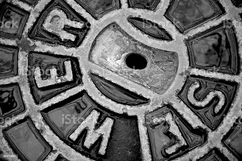 Close-up of a damp iron manhole cover that says sewer stock photo