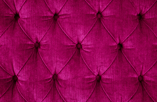Close-up of a dark magenta quilted velvet sofa with upholstered buttons (diamond stitching) / Rautenheftung