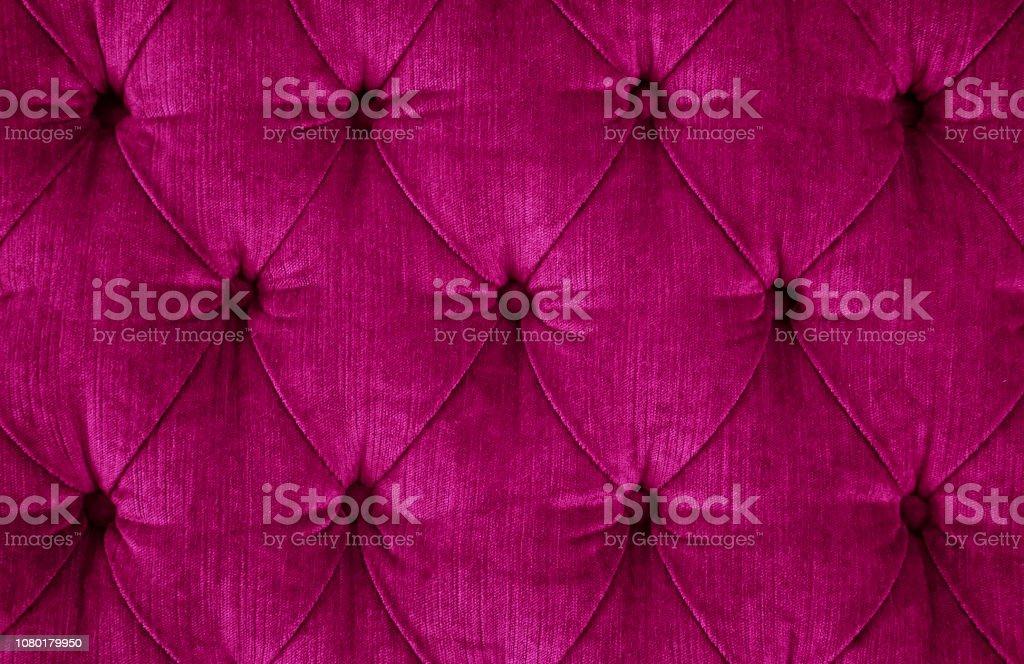 Nahaufnahme eines dunklen Magenta gesteppten samt Sofa mit gepolsterten Tasten (Diamant Nähte) / Rautenheftung – Foto