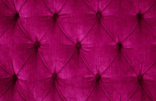 close-up of a dark magenta quilted velvet sofa with upholstered buttons (diamond stitching) / rautenheftung - velvet stock pictures, royalty-free photos & images