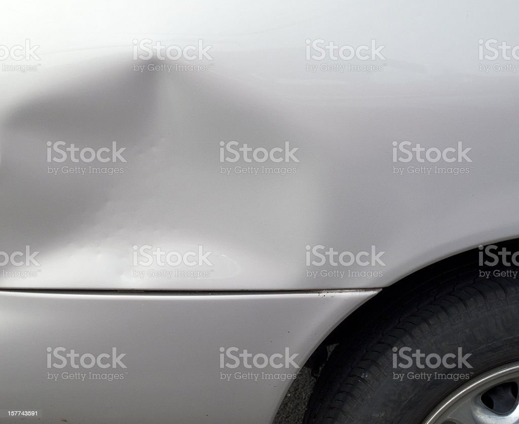 Close-up of a dent in a gray car exterior stock photo