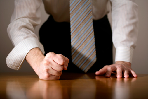 Businessman hitting table with clenched fist.
