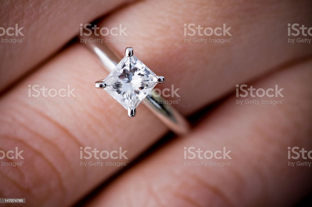 A close-up of a diamond wedding ring on a finger royalty-free stock photo
