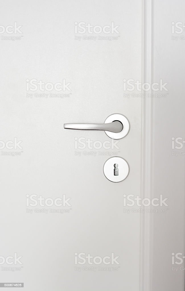 Close-up of a doorknob on white wood door stock photo