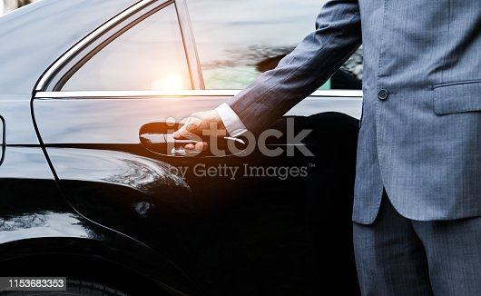 Closeup of a doormans opening a car door.