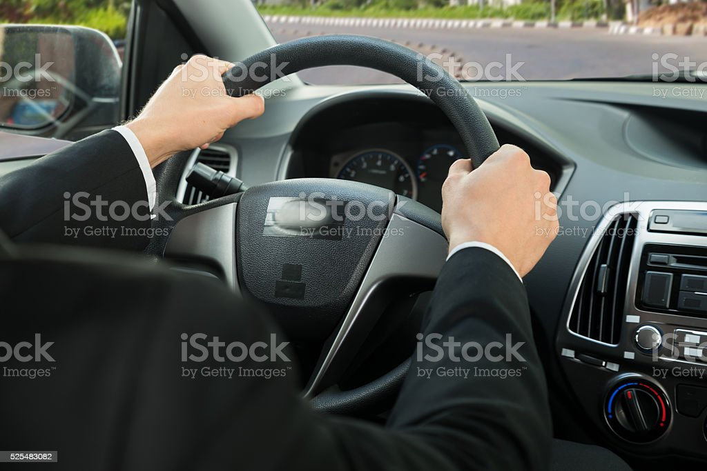 Close-up Of A Driver's Hand On Steering Wheel stock photo