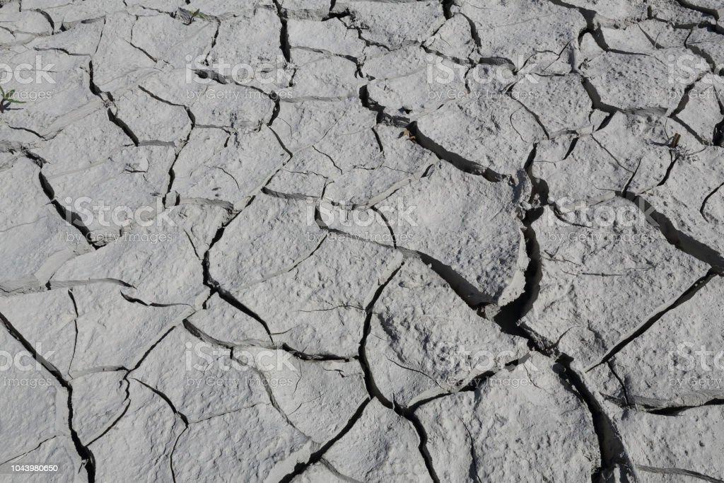 Un primer plano de un suelo de arcilla gris agrietado seco durante un día asoleado caliente en el lago artificial del Mediano en el Pirineo Aragonés Español - foto de stock