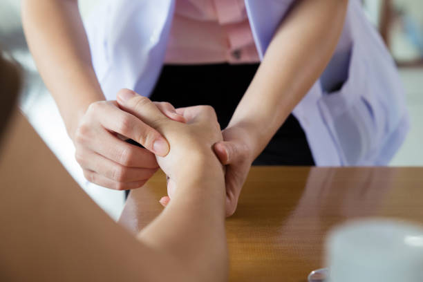 Close-up Of A Female Doctor Examining Patient's Wrist and hand in medical office.