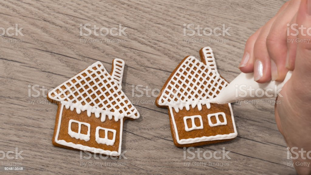 Close-up of a female hand while decorating sweet gingerbreads on a wood table stock photo