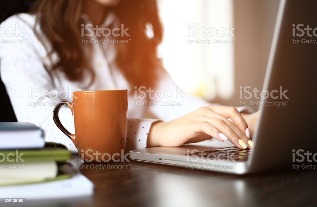 Closeup of a female hands busy typing on a laptop stock photo