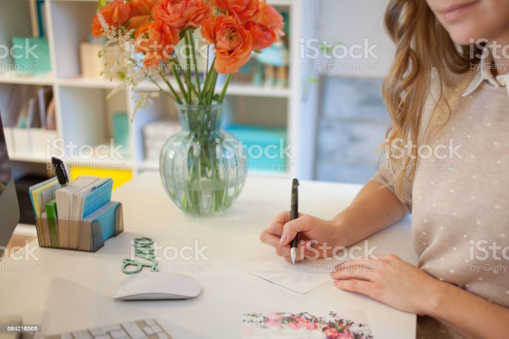 Closeup of a female hands sign the postcard by hand in the office royalty-free stock photo