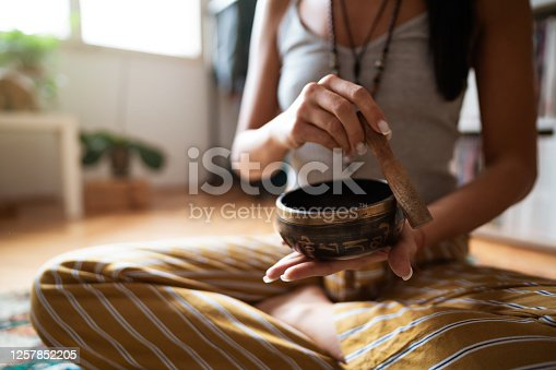 Close-up of a female's hands holding a rin gong and making the sound. Caucasian woman sitting in a lotus position using rin gong at home.