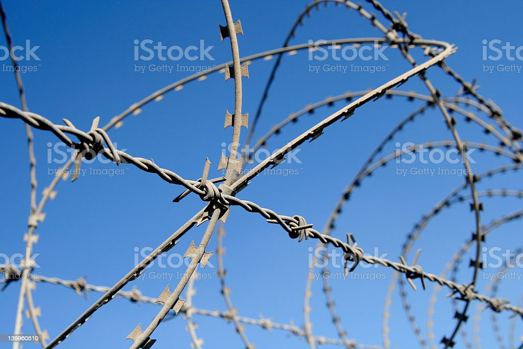 Close-up of a fence with barb wire stock photo