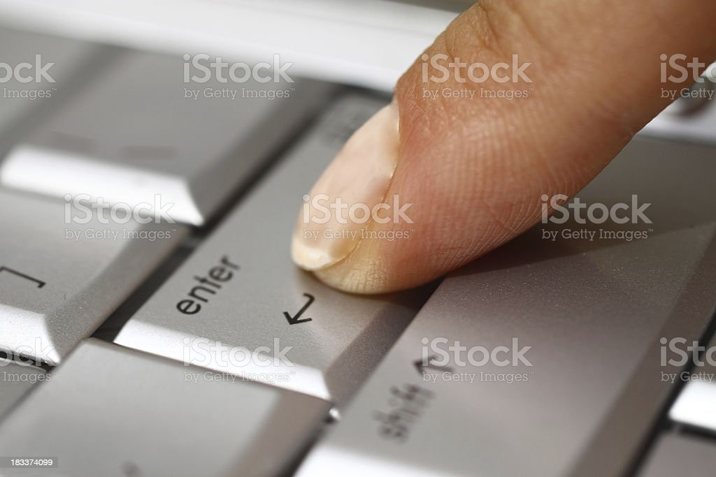 Close-up of a finger pressing the enter key on a keyboard stock photo