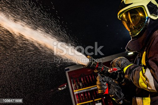Side view of a firefighter in full gear (protective clothing, full face mask helmet) spraying water from a fire hose.