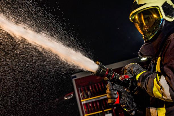 Nahaufnahme eines Feuerwehrmannes Spritzen Feuerwehrschlauch in Betrieb – Foto