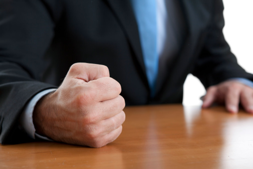 istock Close-up of a fist of a furious businessman on a table 155145637