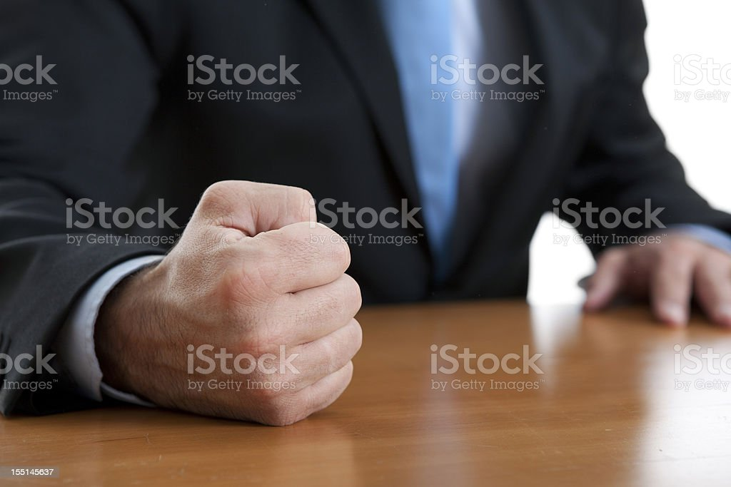 Close-up of a fist of a furious businessman on a table stock photo