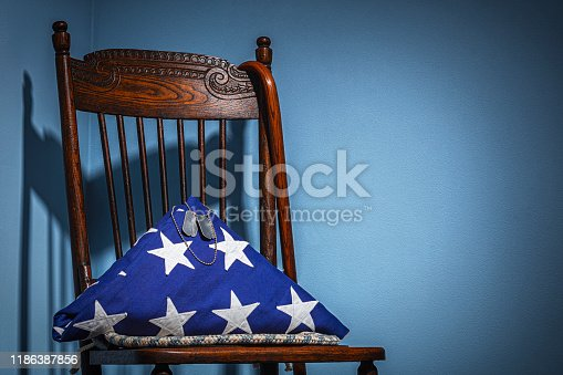 A close-up of a triangle folder American flag from the coffin of a deceased Veteran with blank dog tags in the spot light, sitting in their old wooden chair with wooden cane that is in the corner of an empty room.