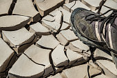 Foot stepping on dry clay of a riverbed. Representation of dry global warming scenario