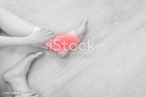 istock Closeup of a Foot with Gauze Elastic Bandage. Asian Woman Ankle Injury Runner. Hands on Injured Legs and Feet with Red Spot on Pain Area Sitting on a Wooden Floor Background from Rupture or Tear. 1142116539