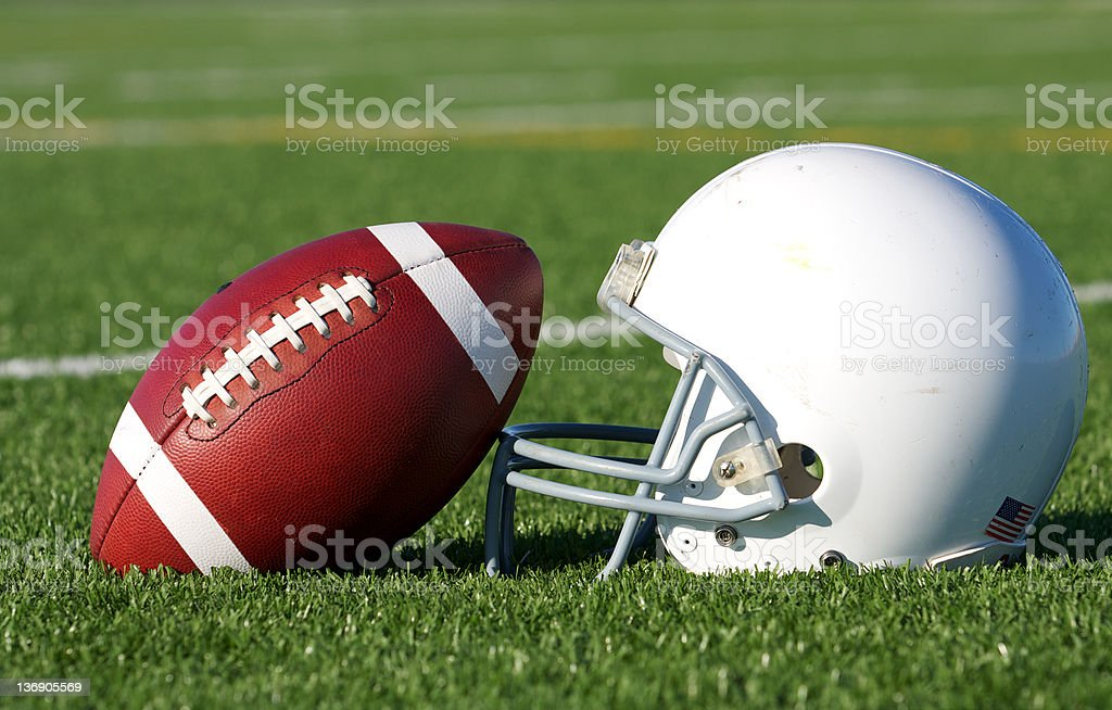 Close-up of a football and a white helmet on the grass stock photo