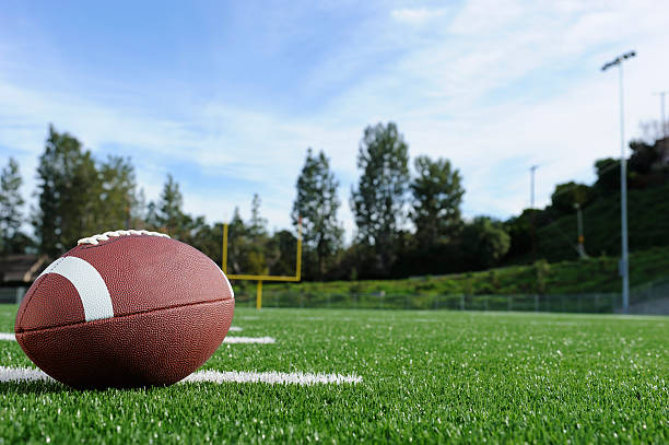 Close-up of a football on a field with view of the goalpost A football on a field american football field stock pictures, royalty-free photos & images