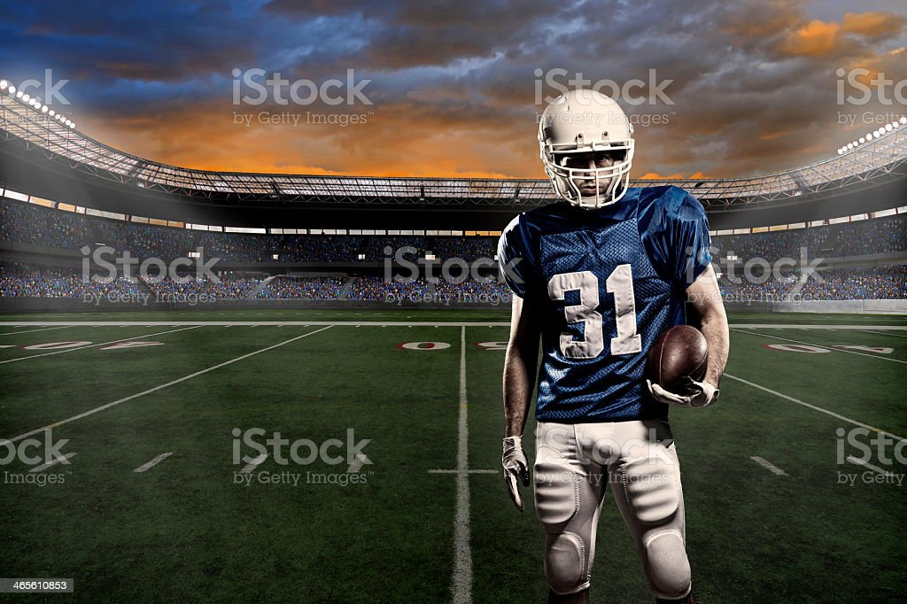 Football player with a blue uniform, in a stadium with fans wearing...