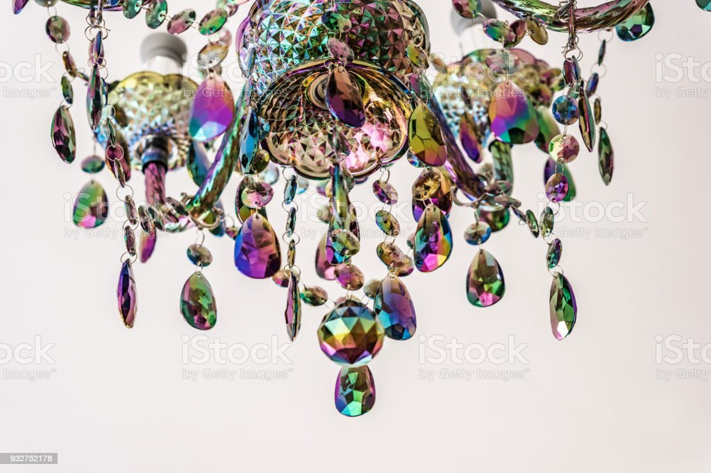 Closeup of a fragment of colored glass chandelier on white background. Color palette of green, purple, yellow and gold. stock photo