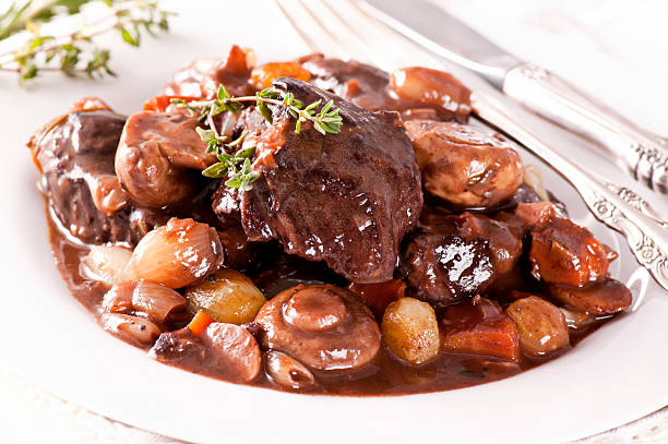 A close-up of a French dish called Boeuf Bourguignon Boeuf bourguignon with vegetable as closeup on a white plate. beef bourguignon stock pictures, royalty-free photos & images