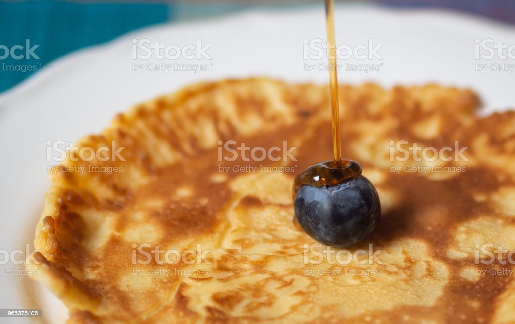 Closeup of a fresh pancake with a single blueberry with maple syrup royalty-free stock photo