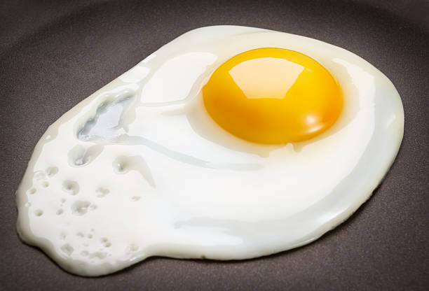 close-up of a fried egg on a black surface - fried egg stock photos and pictures