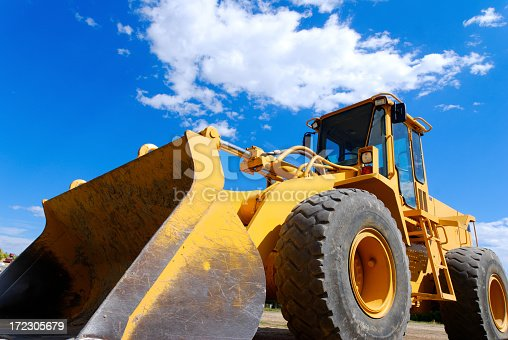 A yellow orange front end loader with a perfect blue sky background.