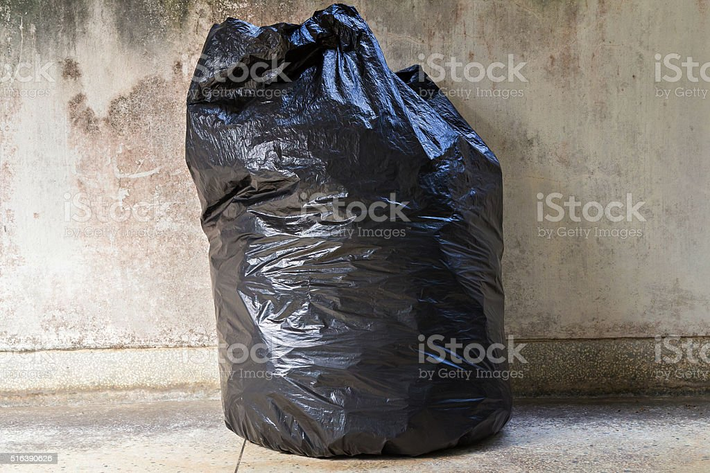 close-up of a full garbage bag on floor stock photo