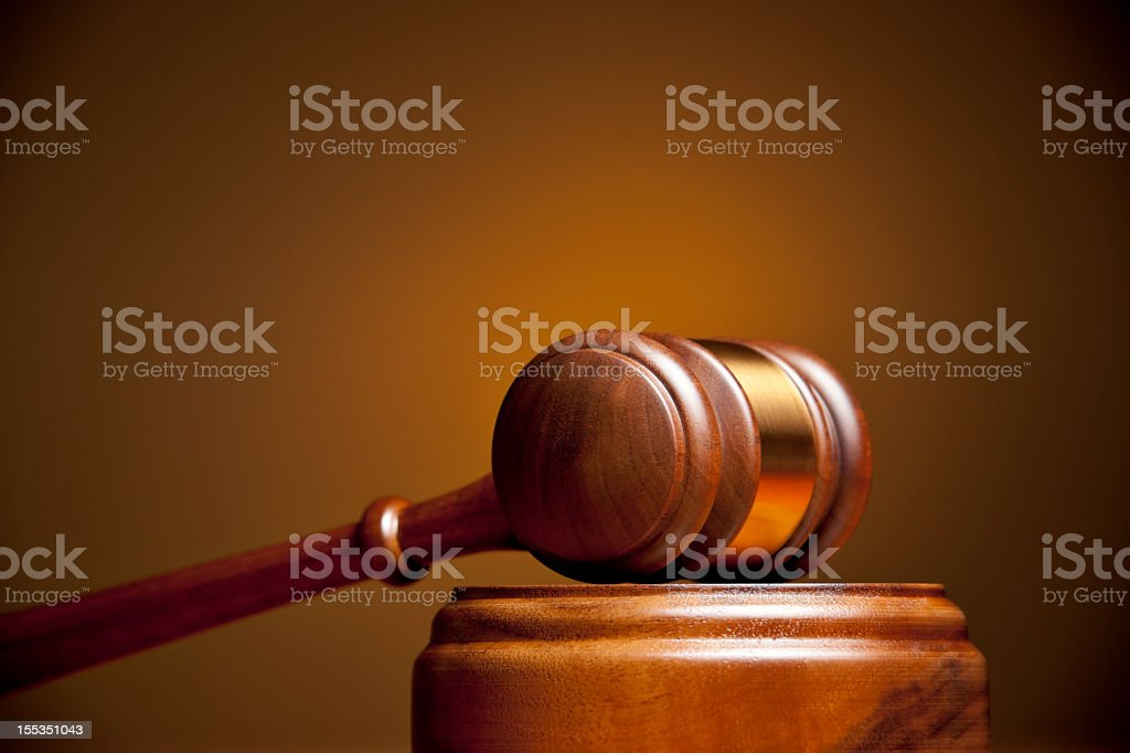Closeup of a gavel resting on a podium stock photo