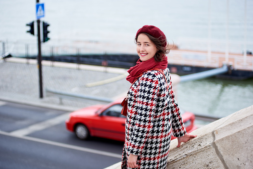 Close-up of a girl descends the steps looking back at the camera. The girl is dressed in a coat, beret and a scarf of one red tone. Below you can see the road. Blurred background