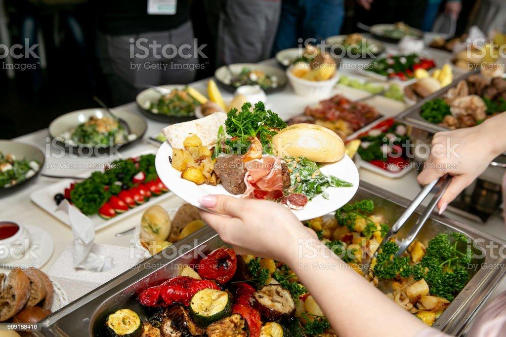 Nahaufnahme eines Mädchens Hand, legte Essen auf einen Teller mit snacks – Foto