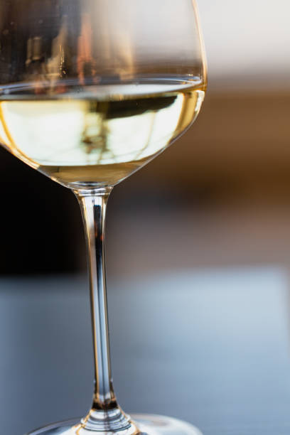 Close-up of a glass of cold white wine on a table. stock photo
