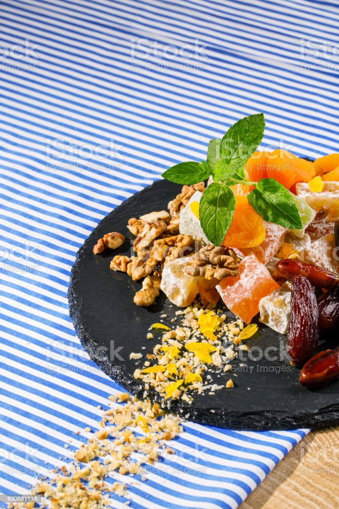 Closeup of a glass plate with date fruits, rahat lokum, walnuts and green leaves of mint on a striped background. stock photo