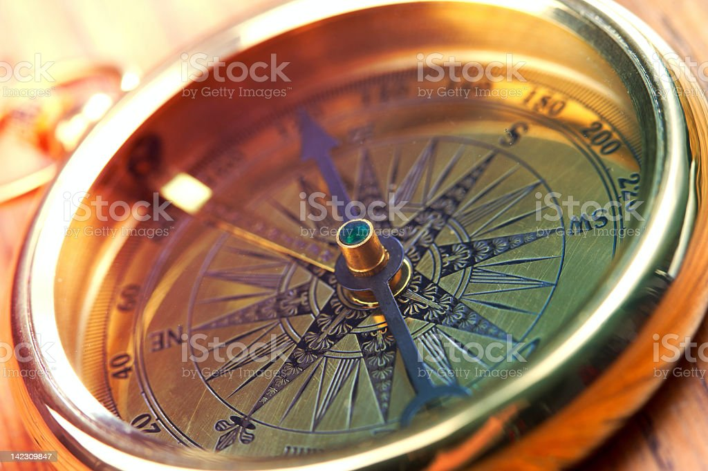 Close-up of a golden compass showing direction stock photo