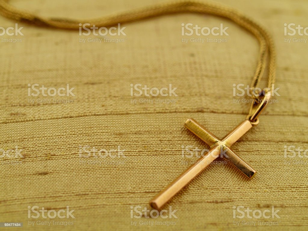 A close-up of a golden cross necklace stock photo