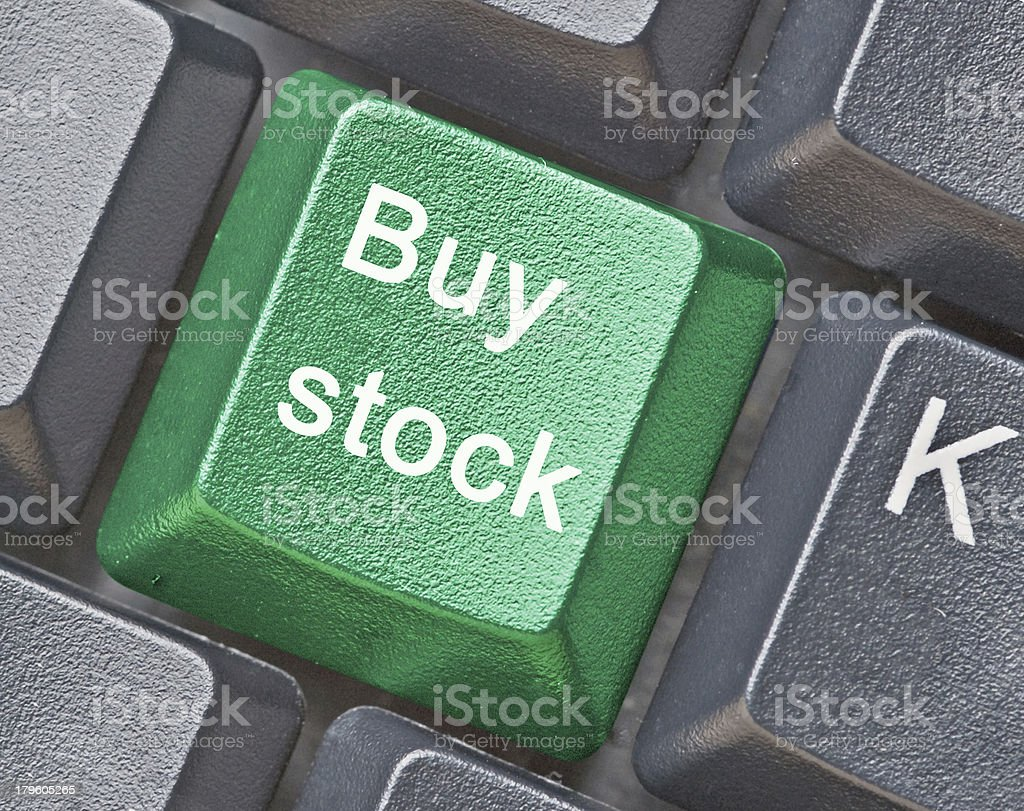 Close-up of a green buy stock button on a black keyboard stock photo