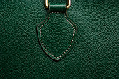 Close-up of a green bag leather texture with slight vignette.